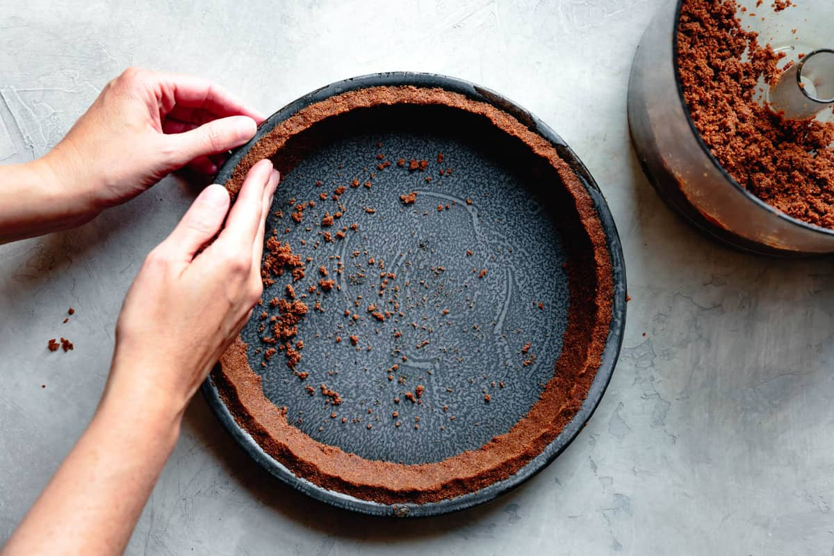 pressing the crumbs into the sides of a vintage pie tin