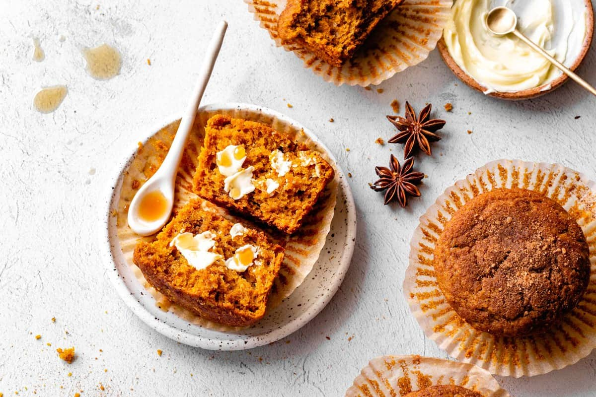 gluten-free pumpkin muffin on a plate, halved, with butter and maple