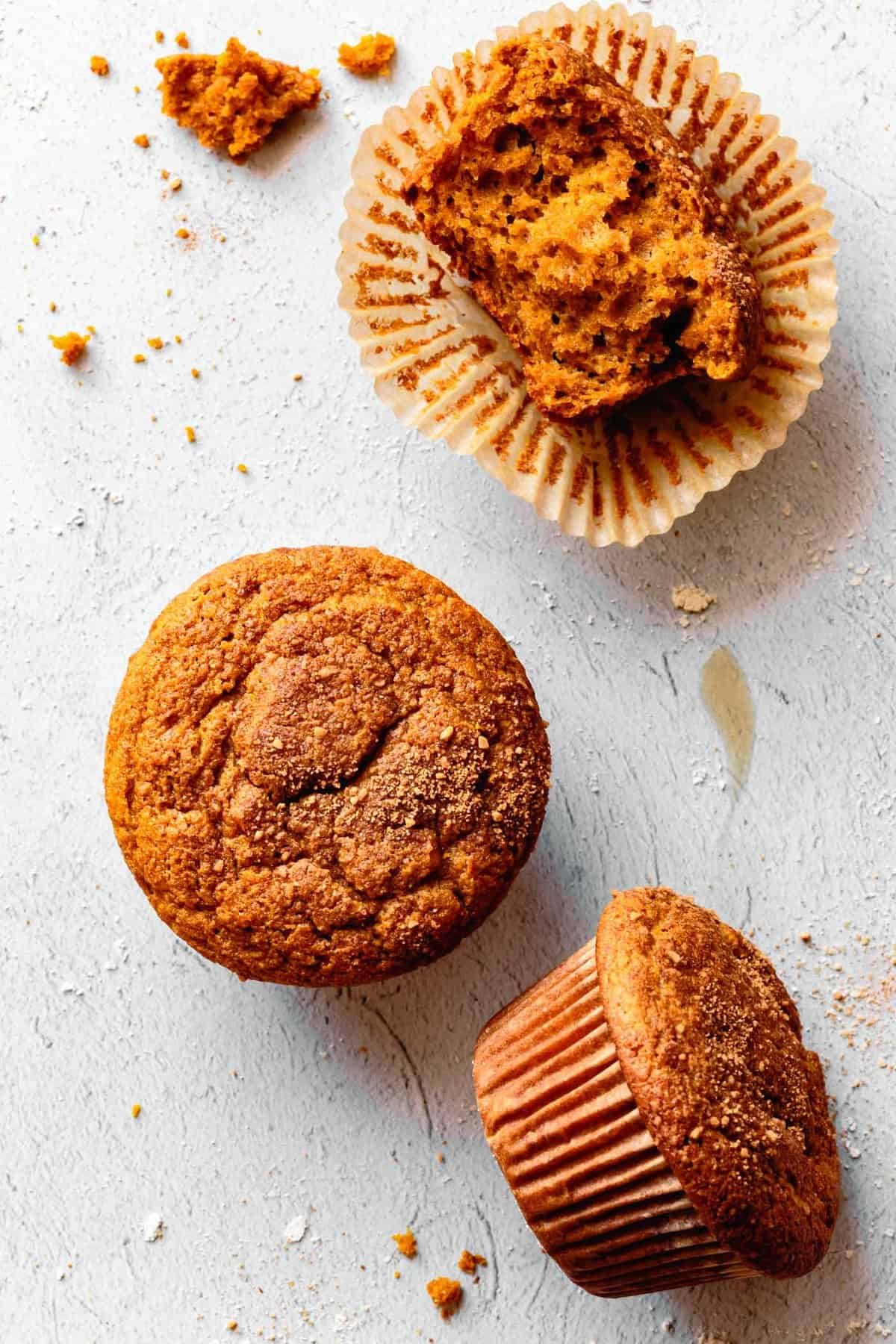 overhead of three healthy gluten-free pumpkin muffins in various stages of disaray