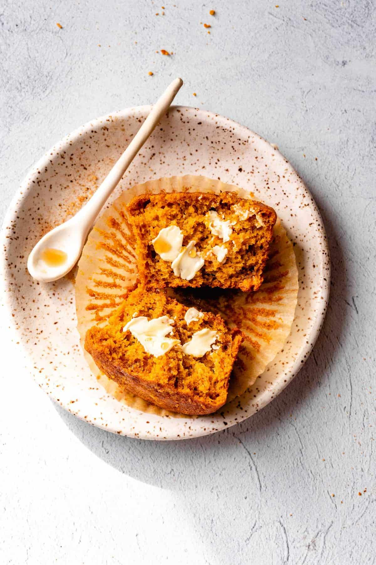 a gluten-free dairy-free pumpkin muffin on a speckled white plate topped with butter and maple