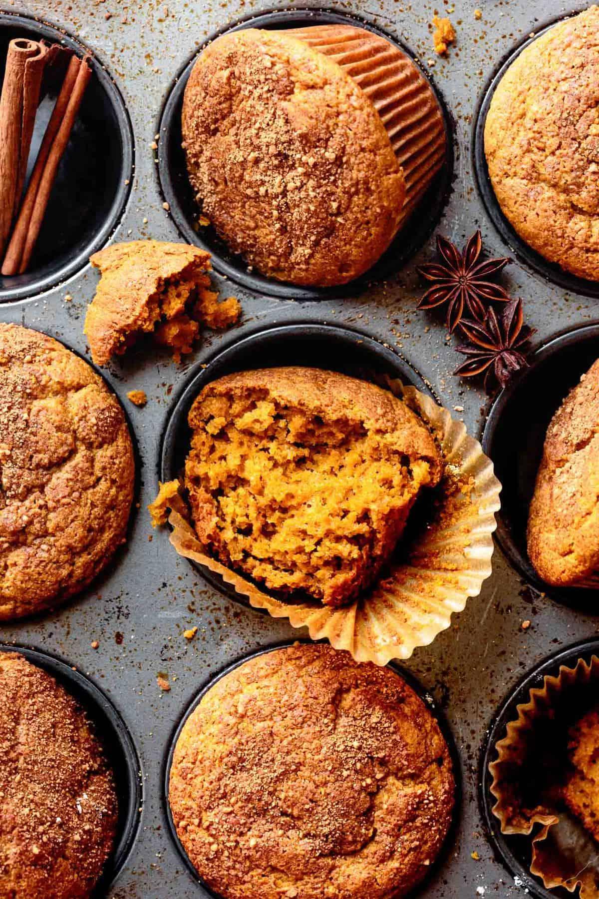 baked gluten-free pumpkin spice muffins in a tin with one broken in half