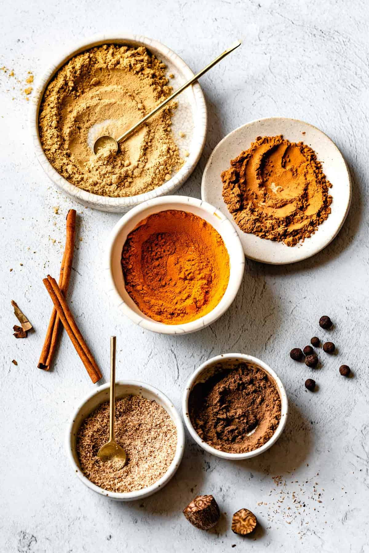 ground spices in small bowls for pumpkin spice seasoning