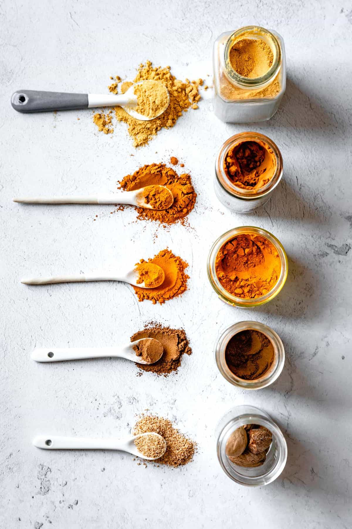 ground spices in jars and small white spoons in two lines for DIY pumpkin pie spice